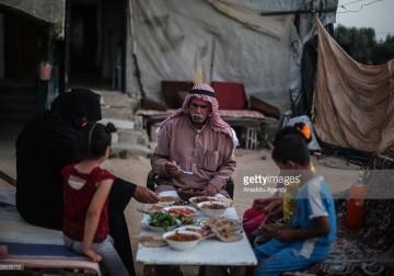 الفلسطيني عاطف الكورا وعائلته يفطروا بجوار حطام منزلهم المدمر .
