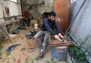 عبد الله العمارين يعمل في محددته بمدينة غزة رغم إصابته في مسيرات العودة