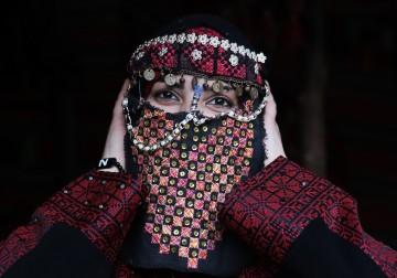 نساء فلسطينيات يرتدين الملابس التراثية خلال معرض فني في غزة