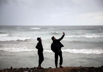 مواطنون على شاطئ بحر غزة وسط الأجواء العاصفة.