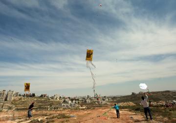 فلسطينيون يطلقون بالونات بألوان علم فلسطين وطائرات ورقية في الجهة المقابلة لسجن عوفر حيث يتواجد فيه الاسرى المضربون عن الطعام