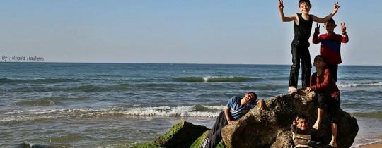 أطفال يلهون على شاطئ مدينة غزة