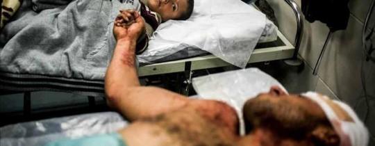 أب فلسطيني يمسك يد طفله الناجي من آلة القتل