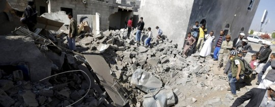 يمنيون يقفون فوق أنقاض بيوت مرتها عاصفة الحزم  قرب مطار صنعاء