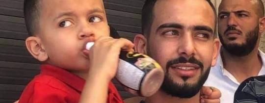 شابٌ من للعيسوية يحمل الطفل محمد ربيع عليان