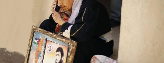 الراحلة والدة الشهيد فارس بارود تحمل صورته في منزلها- ارشيف