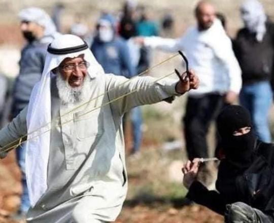 سعيد عرمي يلقى الحجارة على العدو الصهيوني دفاعًا عن أرضه