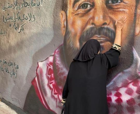 والدة نزار بنات تبكيه أمام جداريةٍ له