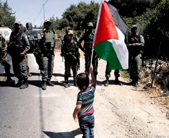 طفلة ترفع علم فلسطيني في وجه مجموعة من جنود الاحتلال- ارشيف