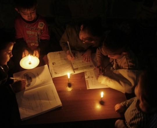 أطفال يذاكرون على إنارة الشموع بغزّة جراء انقطاع التيار الكهربائي